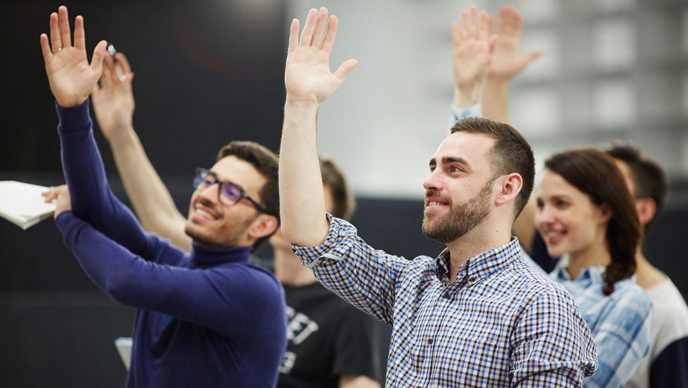 personas levantando la mano en capacitación dth